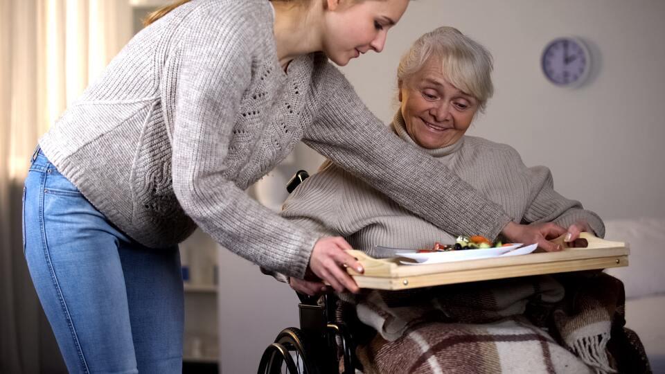Une jeune femme donnant un plateau repas à une autre femme en fauteuil roulant
