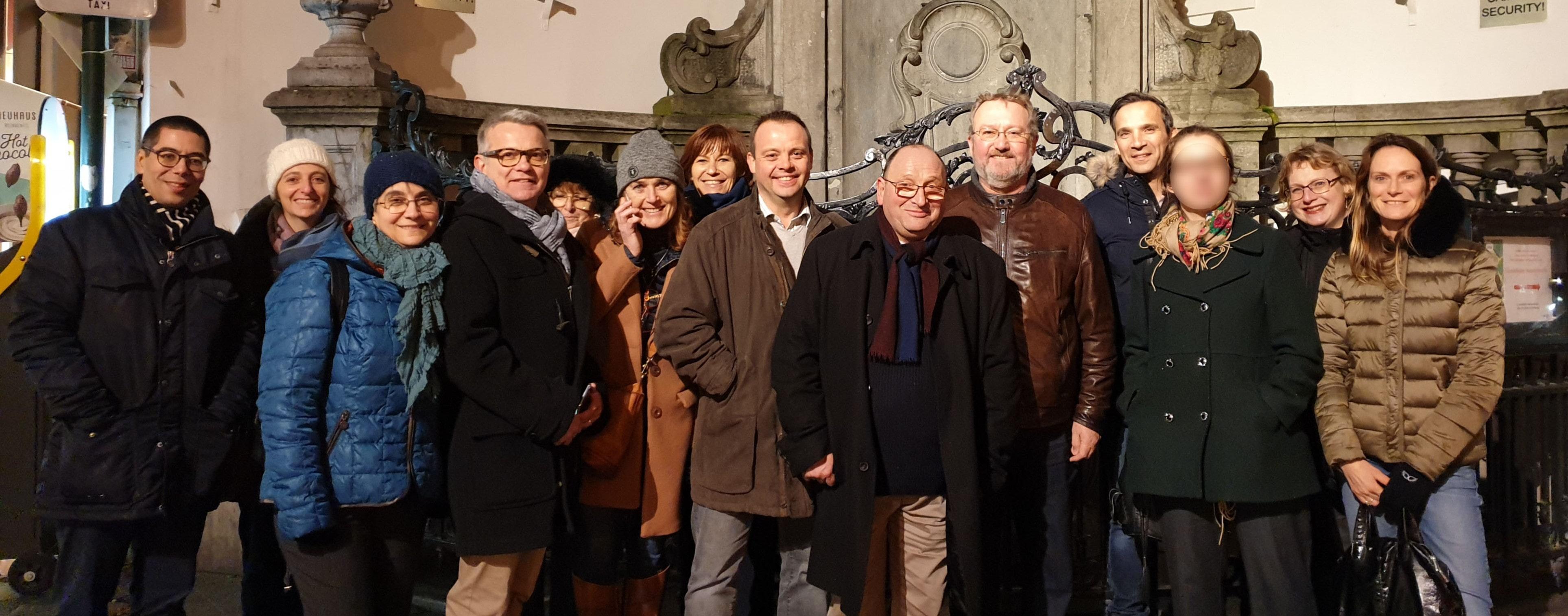Un large groupe de personne prenant la pose devant la Manneken Pis