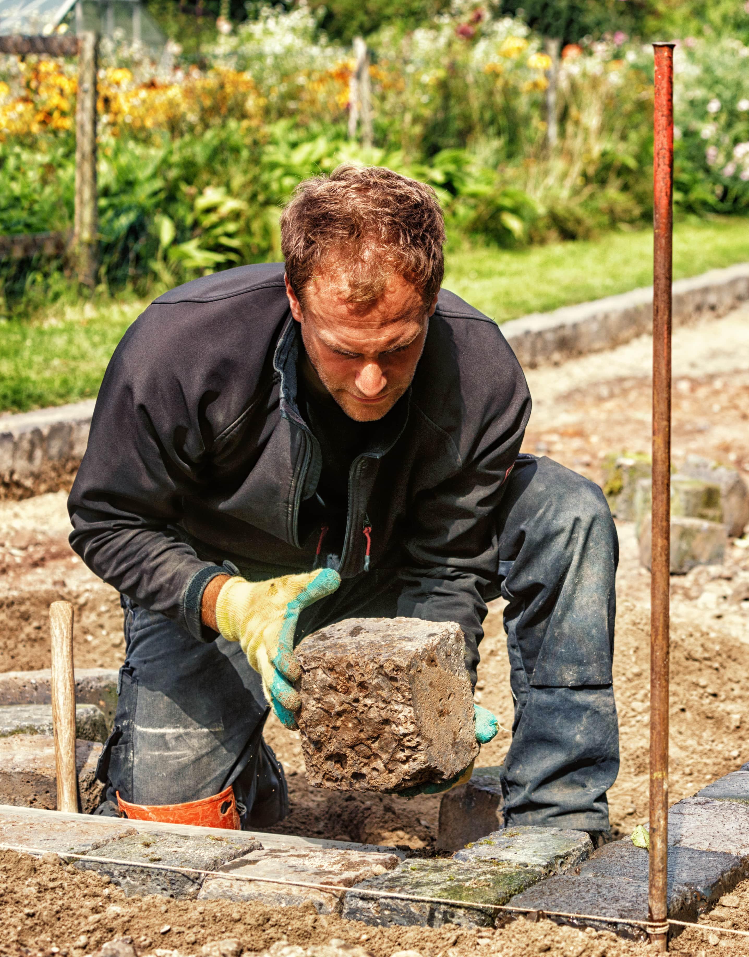 Un homme posant un bloc de pierre au sol
