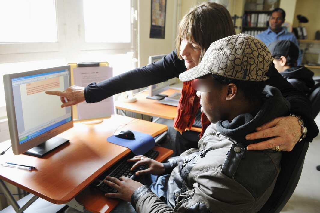 Une femme aidant un jeune travaillant sur un ordinateur