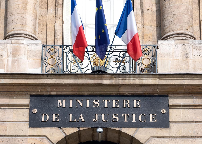 Photo du fronton du Ministère de la Justice, où l'on voit également deux drapeaux français et le drapeau européen