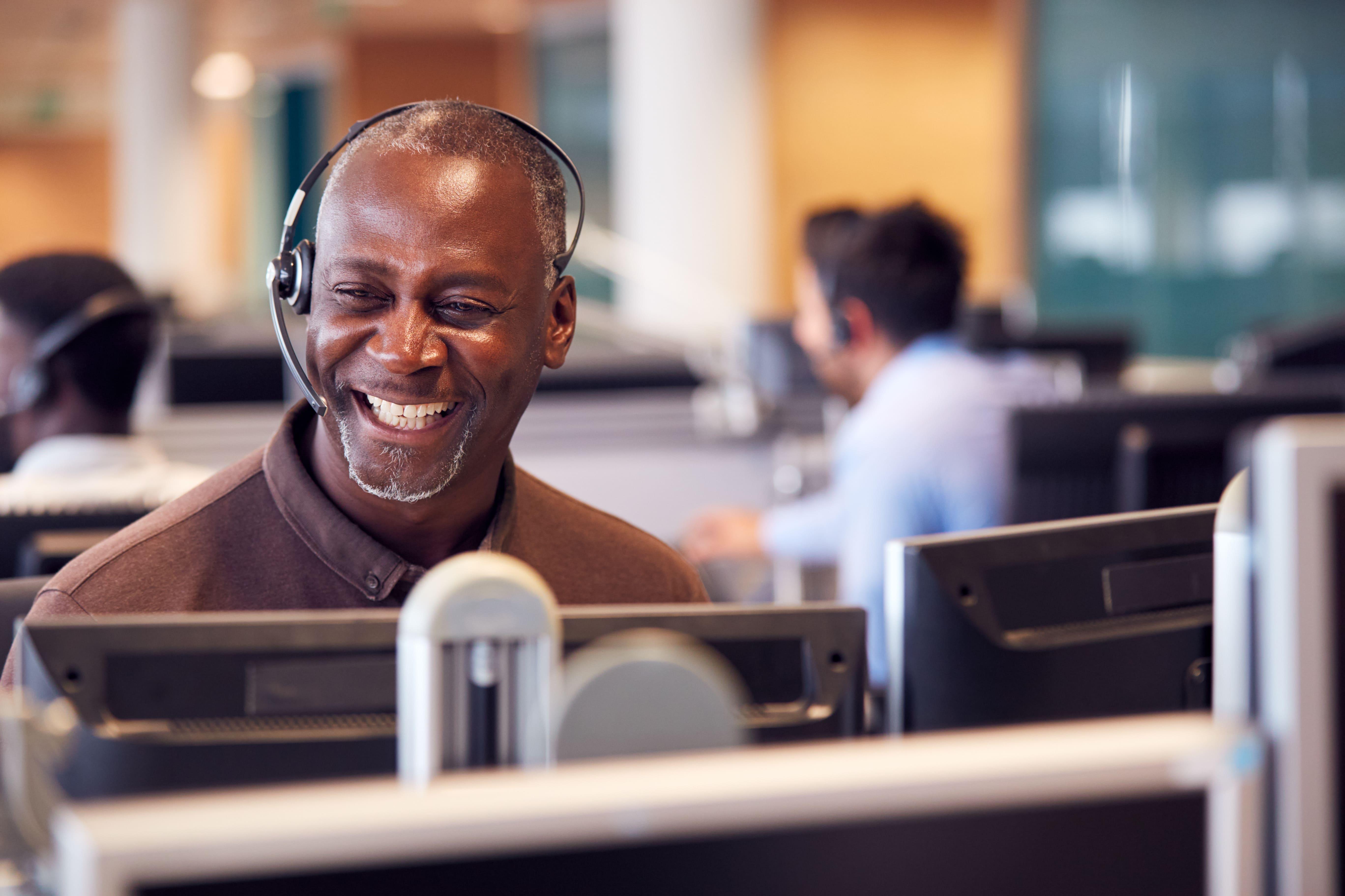 Un homme souriant devant son ordinateur