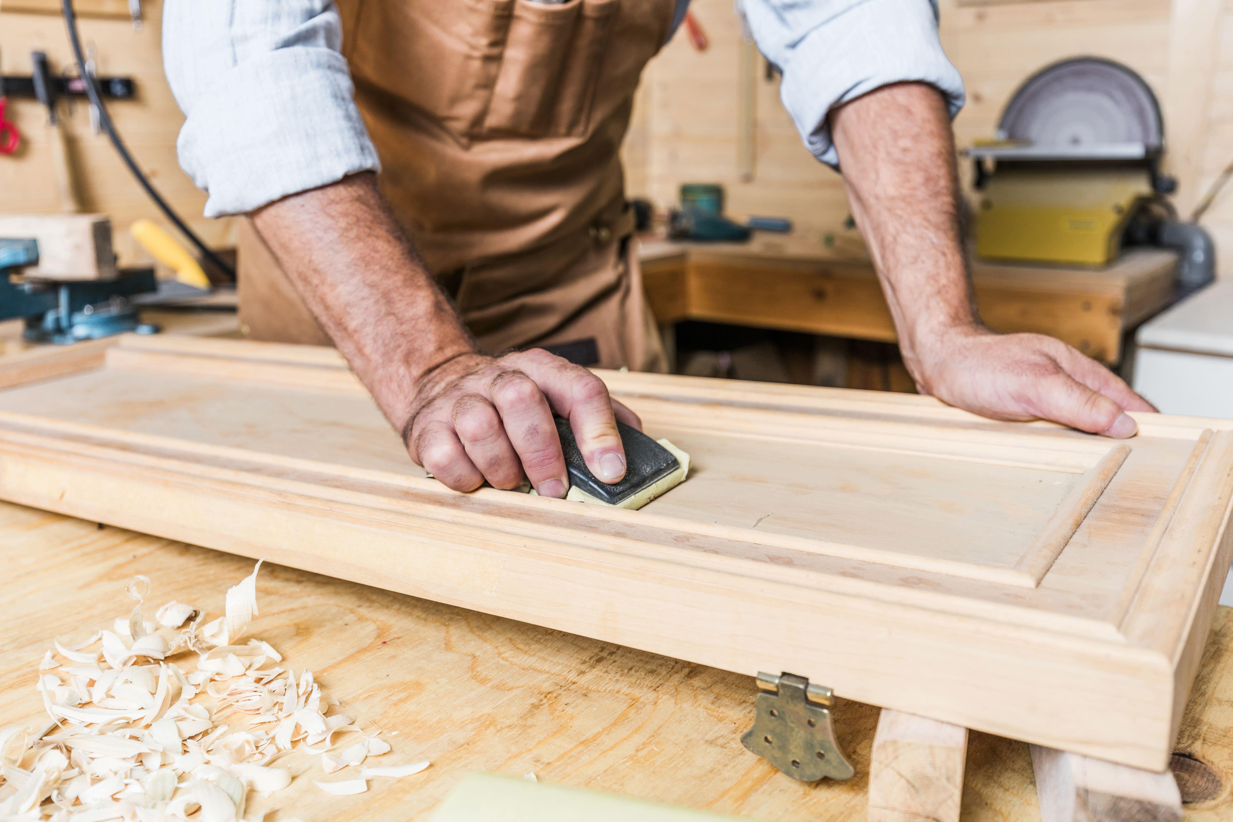 Un menuisier ponce un petite porte en bois