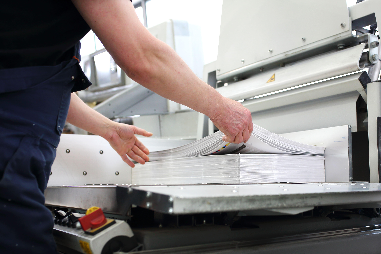 Un ouvrier place des feuilles dans une imprimante